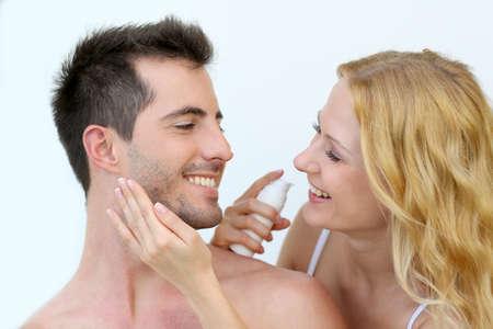 Woman applying sunscreen on her boyfriend's cheeks Stock Photo - 16949355