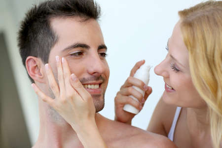 Woman applying sunscreen on her boyfriend's cheeks Stock Photo - 16949341