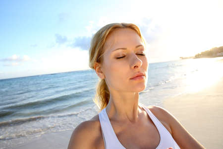 bodycare: Beautiful woman doing yoga exercises by the beach