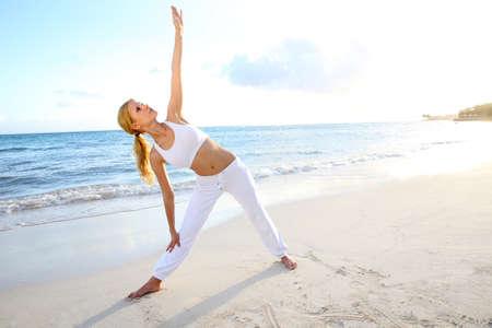 протяжение: Красивая женщина делает упражнения йоги на пляже