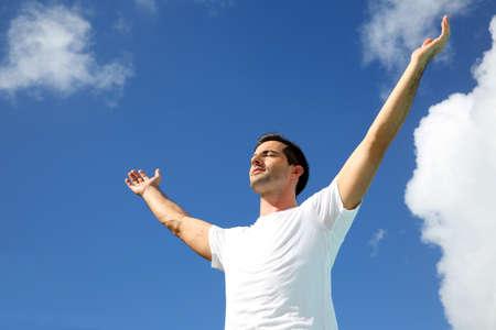 manos levantadas al cielo: Hombre que estira los brazos hacia el cielo Foto de archivo