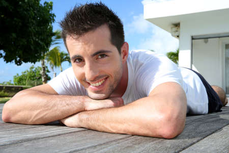 Man relaxing on pool deck after exercising photo