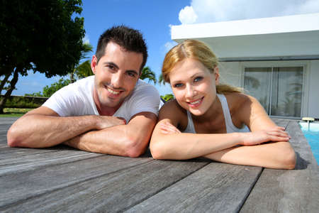 Young couple relaxing on pool deck after exercising photo