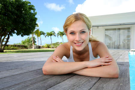 Smiling woman laying on pool deck after exercising photo