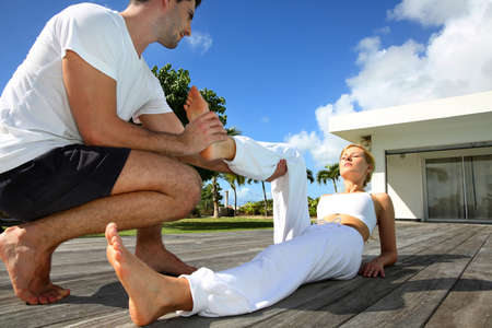 Woman with personal trainer exercising outside photo