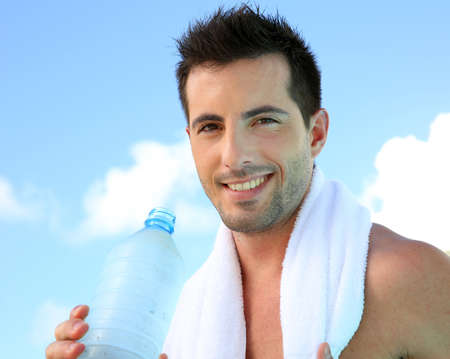 Handsome man drinking water after exercising photo
