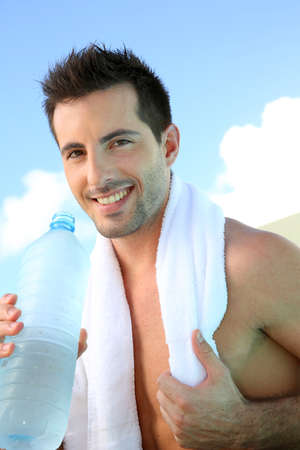 looking after: Handsome man drinking water after exercising Stock Photo