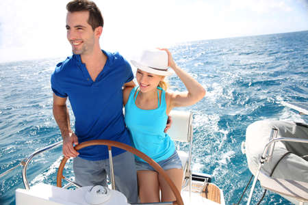 recreation yachts: Young couple navigating on a yacht in caribbean sea