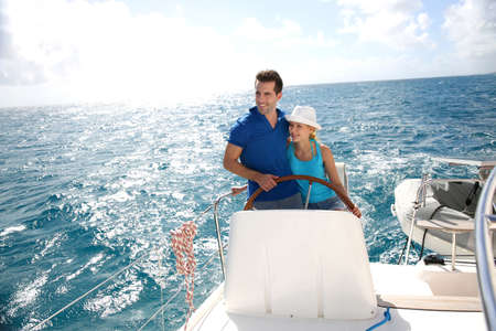 yachting: Young couple navigating on a yacht in caribbean sea