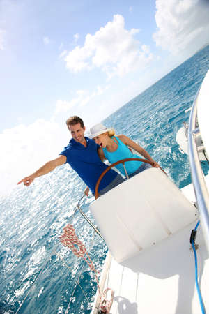 Young couple navigating on a yacht in caribbean sea photo