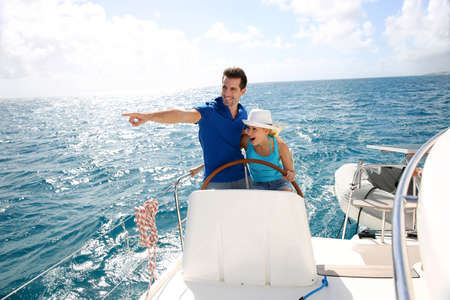 sail boat: Young couple navigating on a yacht in caribbean sea