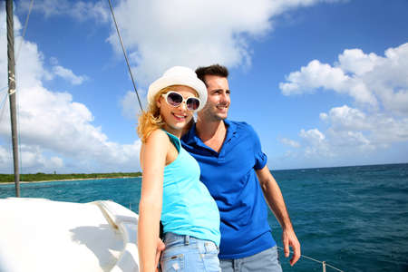catamaran: Smiling rich young couple on a sailboat in Caribbean sea