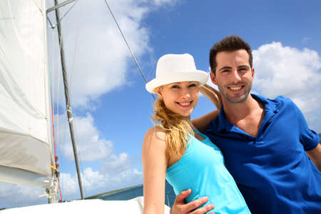 recreation yachts: Smiling rich young couple on a sailboat in Caribbean sea