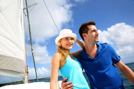 yachting: Smiling rich young couple on a sailboat in Caribbean sea