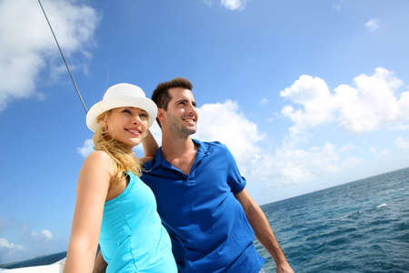 cruising: Smiling rich young couple on a sailboat in Caribbean sea