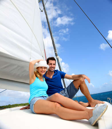recreation yachts: Cheerful couple cruising on a catamaran in Caribbean sea Stock Photo