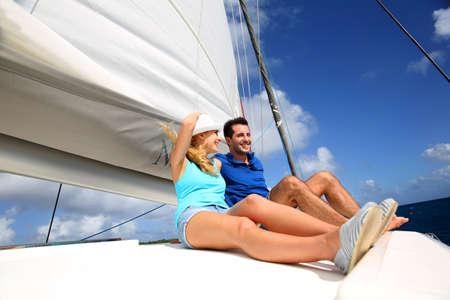 cruising: Cheerful couple cruising on a catamaran in Caribbean sea Stock Photo