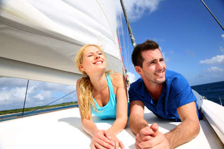 catamaran: Smiling couple relaxing on a yacht by sunny day