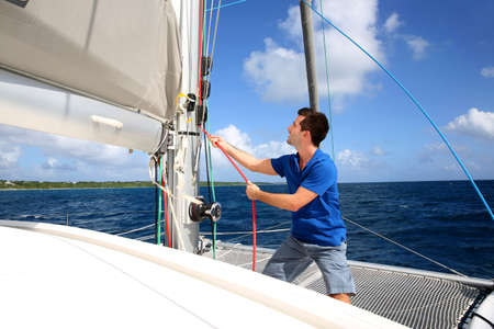Hombre joven levantando la vela de catamarán de crucero durante