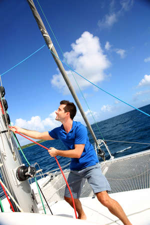 cruising: Young man lifting the sail of catamaran during cruising