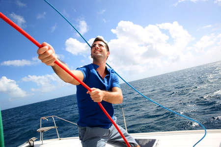 Young man lifting the sail of catamaran during cruising photo