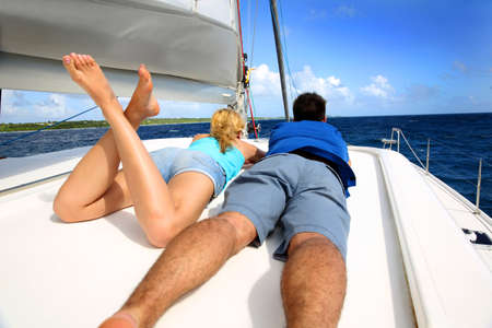 catamaran: Couple relaxing on a sailing boat while cruising
