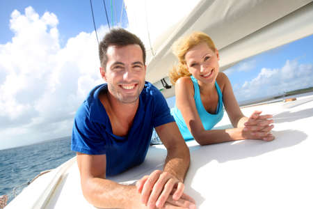 happy rich woman: Cheerful couple cruising on a sail boat