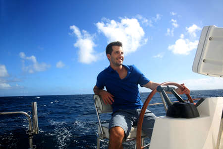 catamaran: Smiling young sailor navigating in Caribbean sea Stock Photo