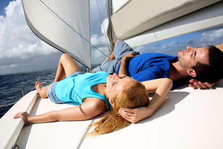 catamaran: Young couple relaxing on sailboat deck