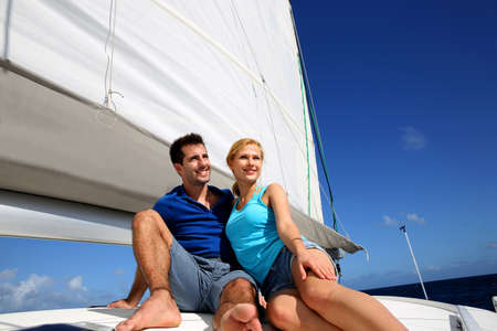 catamaran: Portrait of couple sitting on the top of sailing boat