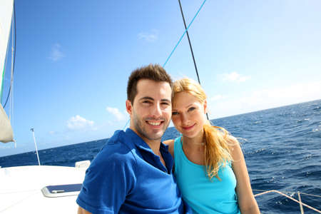 sailing boat: Portrait of couple sitting on the top of sailing boat