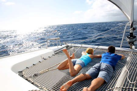 catamaran: Couple relaxing on catamaran net looking at the sea Stock Photo