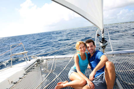 cruising: Couple relaxing on catamaran net looking at the sea Stock Photo