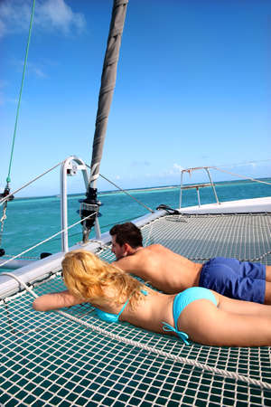 Young couple relaxing at the front of yacht photo