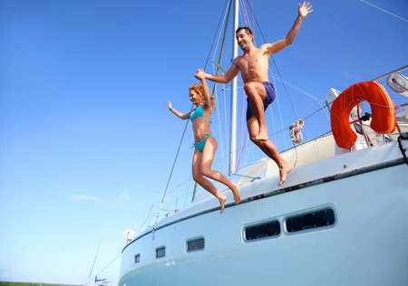 sail boat: Young couple jumping in water from yacht Stock Photo