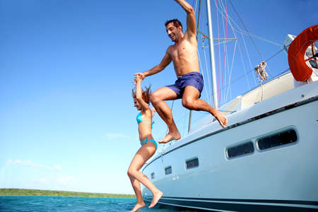 adventure sports: Young couple jumping in water from yacht Stock Photo