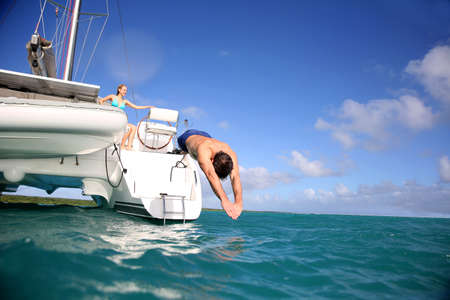 recreation yachts: Man diving from catamaran deck into the sea Stock Photo