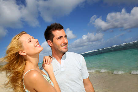 suntanning: Young couple walking on a sandy beach
