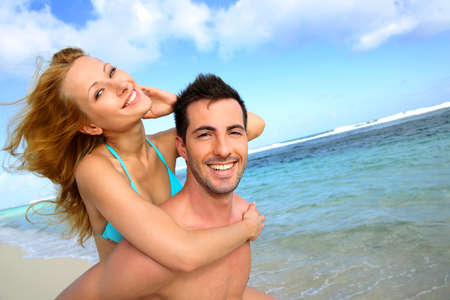 Man giving piggyback ride to girlfriend at the beach photo