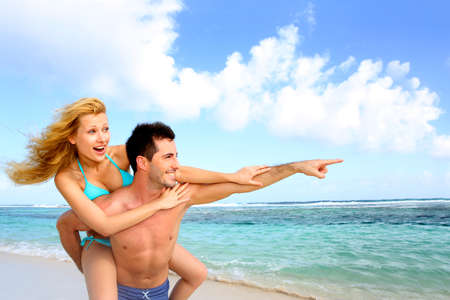 bikini couple: Man giving piggyback ride to girlfriend at the beach Stock Photo