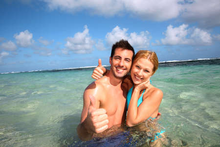 Couple in a caribbean lagoon showing thumbs up photo