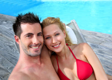 Couple relaxing in long chairs by swimming-pool photo