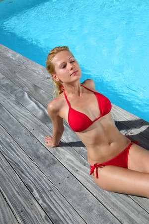 pool deck: Blond woman in red bikini relaxing by pool