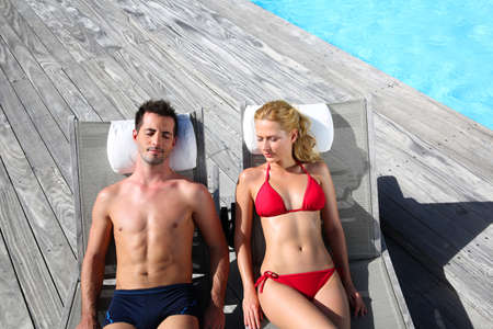 Fancy couple relaxing in longchairs by swimming pool photo