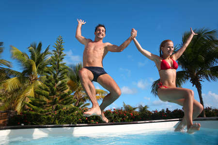 pool fun: Young couple jumping in swimming pool