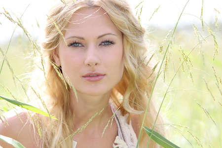 blonde  blue eyes: Glamorous young woman standing in meadow