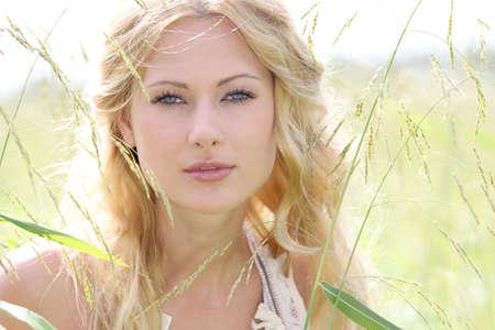 rubia ojos azules: Mujer joven atractiva permanente en la pradera Foto de archivo
