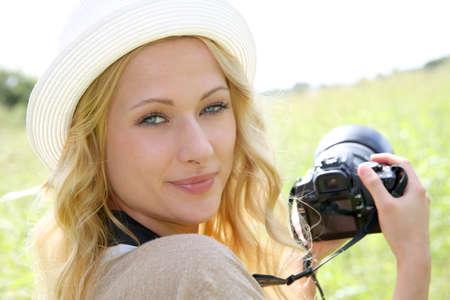 Portrait of adventure girl using photo camera in nature photo