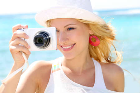 Cheerful girl talking pictures with digital camera photo