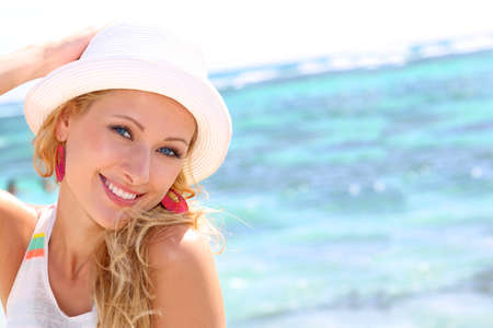 Beautiful girl wearing hat at the beach photo
